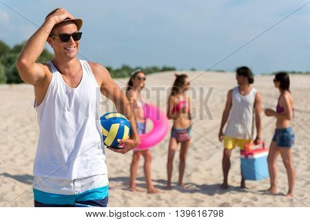 Glad to be here. Cheerful handsome man holding ball for volleyball and smiling while resting with his friends on the beach