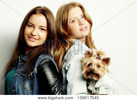 two happy teenage sisters with Yorkshire Terrier