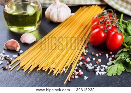 Pasta ingridients and spice on black slate surface.