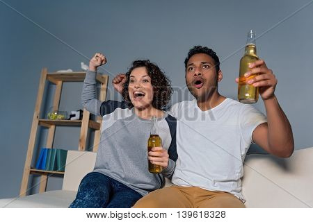 Watching decisive match. Beautiful couple sitting at home and watching football match of their favorite team, holding beer