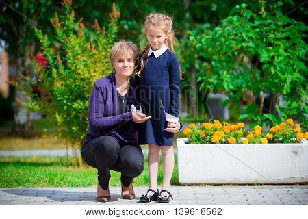 Grandmother brings her little granddaughter to school.