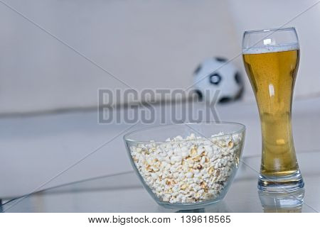 Close up of glass of beer standing on table next to popcorn and soccer ball in background