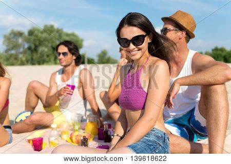 Full of emotions. Positive content beautiful woman sitting on the sand with her friends while having a picnic on the beach