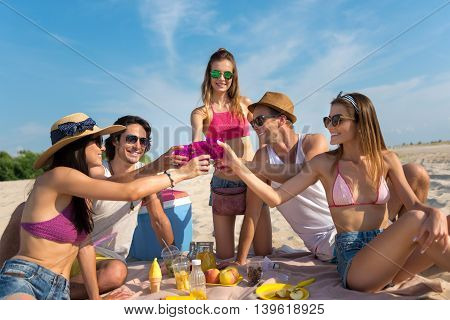 Real emotions. Positive delighted smiling friends sitting on the sand and drinking while having fun on the beach
