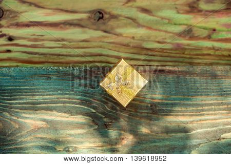Gift box with golden wrapper ribbon and bow on wooden plank on timber background