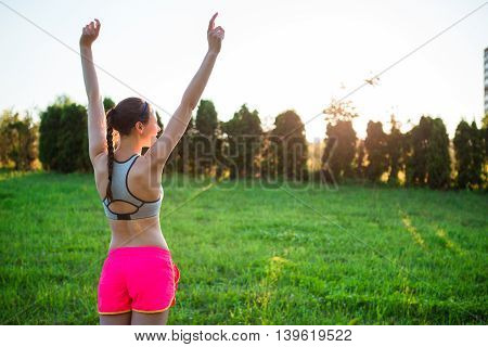 Young smiling girl doing sporty exercises outdoors