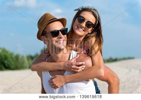 Pleasant time. Cheerful handsome smiling man holding his girlfriend on the back and expressing joy while resting on the beach together