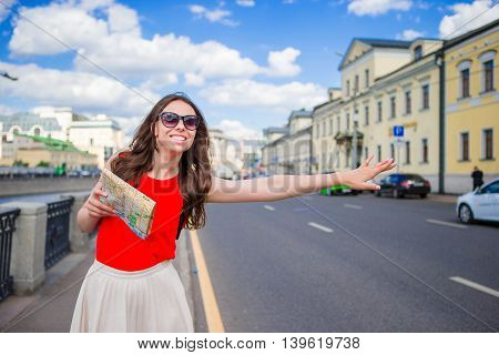 Young happy girl with city map catch a taxi on the street