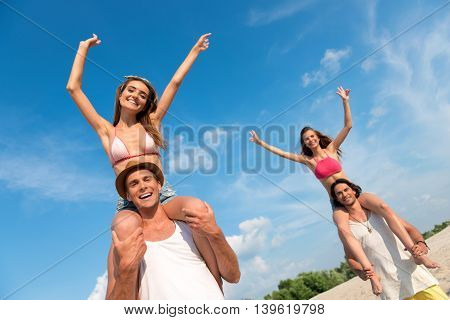 Feel the taste of summer. Pleasant overjoyed smiling men holding beautiful girls on the shoulders while having fun on the beach