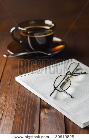 Notepad And Glasses Do Not Lie Wooden Table, And Next To A Cup Of Coffee.