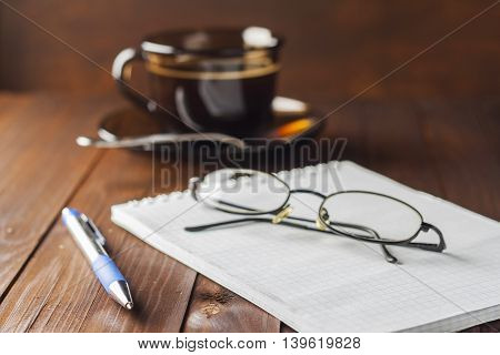Notepad With Pen And Glasses Do Not Lie Wooden Table, And Next To A Cup Of Coffee.