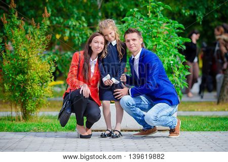 Mother and father brings little daughter to school.