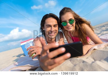 Put a smile on. Cheerful delighted friends using cell phone and making selfies while resting on the sand