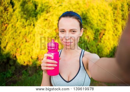 Young woman drinking water after running outside. Female fitness model training outside in the park