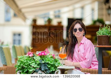 Young woman drinking aperol in a cafe outdoors