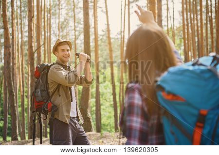 Happy loving couple is making touristic trip in forest. Woman is standing and gesturing. Man is holding binoculars and smiling