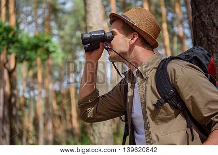 Cheerful traveler is enjoying the nature. He is looking through binoculars with joy. Man is carrying backpack