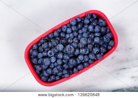 Overhead view of a red basket full of ripe blueberries on natural marble stone counter.