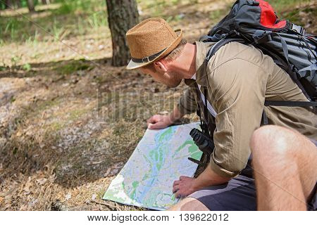 Serious young man is reading touristic map. He is sitting on ground in forest with backpack