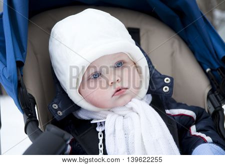 Closeup baby boy is lying in a stroller in winter clothes