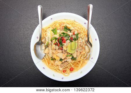 Bowl of spicy noodles on black background