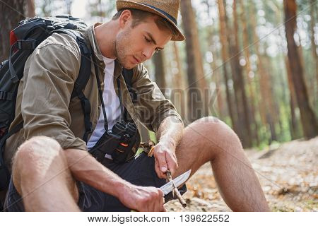 Serious young tourist is cutting a wood stick with knife. He is sitting on ground in nature