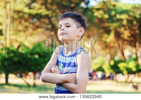 Portrait of a confident six year old boy in the park Looking Directly to the Camera. At the elbow there is a wound clenched fists.