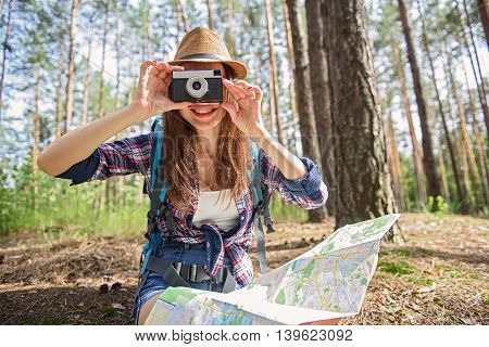 Carefree young tourist is taking photos of nature in forest. She is holding map and sitting. Woman is smiling with happiness