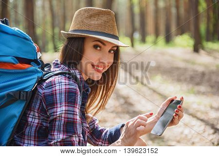 Joyful young woman is searching for location with smartphone navigator. She is looking at camera and smiling