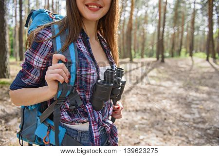 Joyful young woman is hiking in forest with backpack. She is standing and smiling