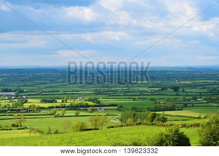 A photo encapsulating the beauty of the green Irish rural landscape by portraying the vast green fields of Ireland's countryside