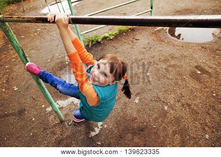 Portrait of a young girl hanging like monkey on the bar at the playground.