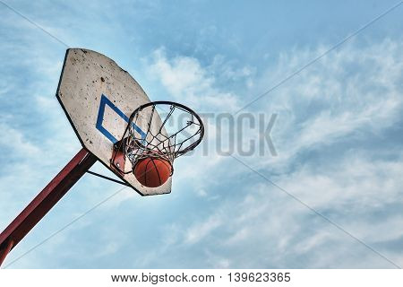 Basketball in the ring against the sky.