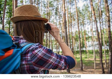 Young woman is making touristic journey in forest. She is looking into binoculars at landscape