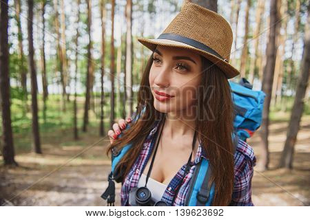Female tourist in relaxing in nature. She is standing and smiling with happiness