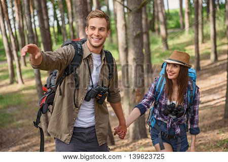 Look at this wonderful nature. Pretty loving couple is making journey in forest. They are holding hands and smiling. Man is pointing finger sideways
