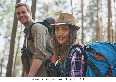 Cheerful loving couple is hiking in forest. They are looking at camera and smiling