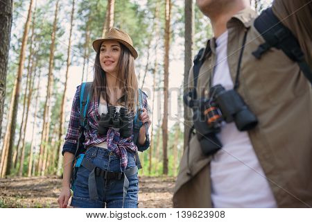 Cheerful friends are making touristic journey in forest. Woman is looking forward with interest and smiling