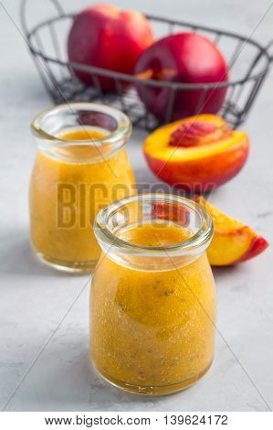 Smoothie with nectarine orange juice chia seeds and honey in glass jar vertical concrete background