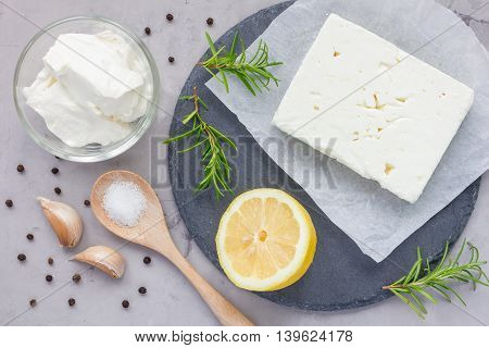 Ingredients for feta cream cheese rosemary lemon and garlic dip on slate board top view