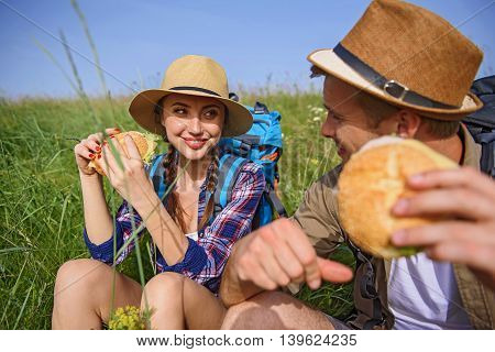 Joyful young tourists are eating sandwich on break. They are talking and smiling