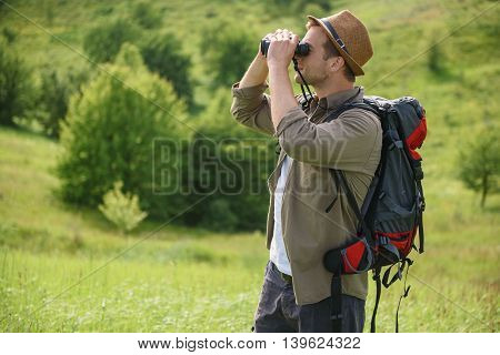 Young man is enjoying nature on field. He is standing and looking into binoculars with interest