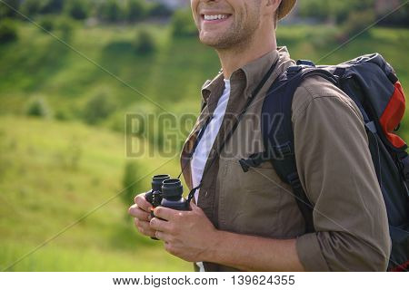Happy male tourist is relaxing in nature. He is standing in meadow and smiling. Man is holding binoculars