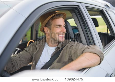 Cheerful young man is making trip by car. He is sitting at steering wheel and enjoying nature. Adventurer is smiling