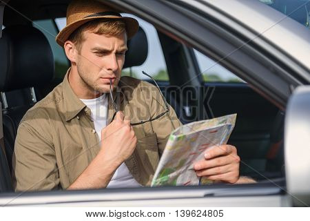 Male tourist is searching place of destination. He is reading map with seriousness. Man is sitting in car