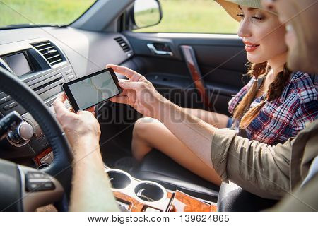 Young tourists are using smartphone navigation map in car. They are sitting and smiling