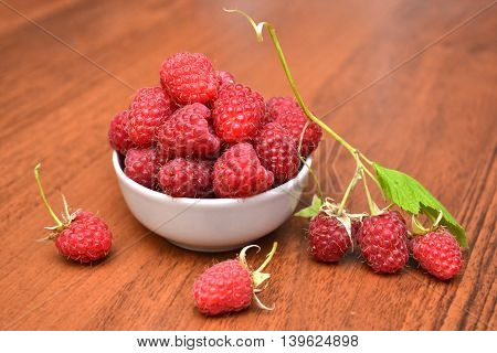 Raspberries in white plate on a wooden table. Raspberries brunch on the table. Natural texture.