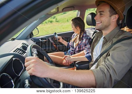 Happy loving couple is making trip in countryside. They are sitting in car and holding hands. Man is smiling. Woman is using mobile phone