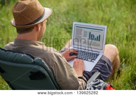 Cheerful male freelancer is typing on laptop in nature. He is sitting on folding chair in meadow and relaxing