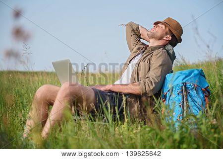 Young man is relaxing in nature. He is holding laptop and sitting on chair. His eyes are closed with pleasure